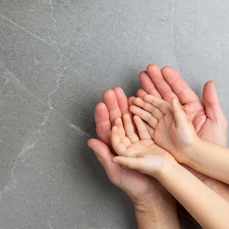 Adult hands holding kid hands, Family Help Care Concept, small hands in fathers hand. on gray background