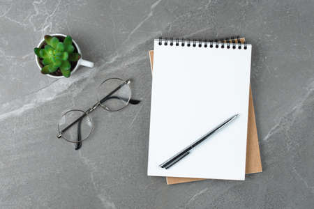 notebook with glasses on the marble table, flat lay business concept. Stock fotó