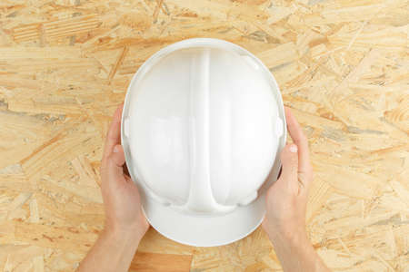 construction helmet in hands on a wooden board top view. osb board as background