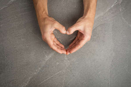 hands hold heart shaped on gray background, the concept of love and care for loved ones and needy. AIDs day concept Zdjęcie Seryjne
