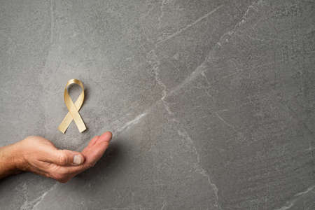 golden ribbon childhood symbol of the fight against cancer in male hands on a gray background. concept of helping patients with sarcoma and bladder cancer.