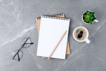 School notebook with glasses and coffee on table on the marble table. Flat lay business concept.