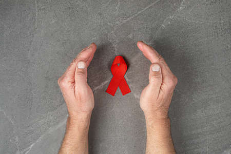 AID red ribbon in hand on gray background, symbol of the fight against HIV, AIDS and cancer. concept of helping those in need