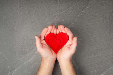 red heart in hands on gray background, the concept of love and care for loved ones and needy.