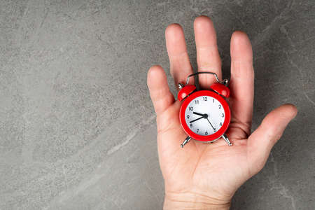 Red alarm clock on hands top view on a gray background. Business concert a lot of free space, flat lay