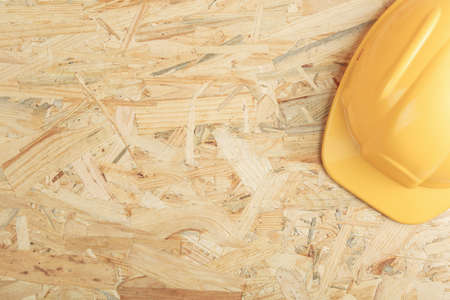 construction helmet on a wooden board top view. osb board as background flat lay.