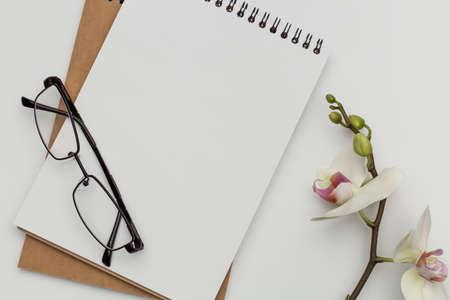 Notizbuch auf weißem Tisch mit Geschenkbox und Bleistift