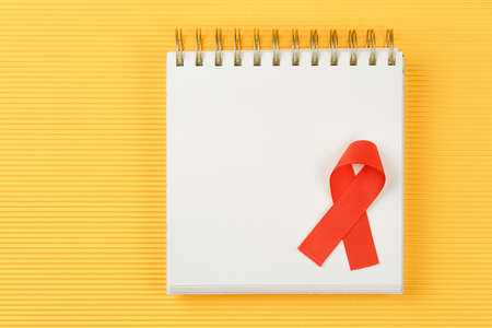 red aids ribbon on open notebook isolated on yellow background, aids day and symbol of helping cancer patients vertical view