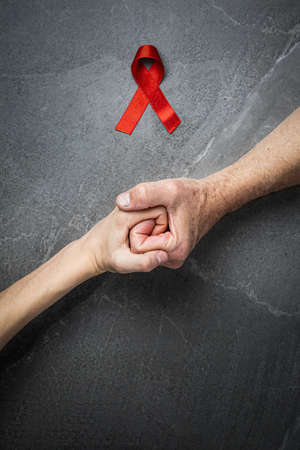 AID red ribbon in hand on dark gray marble background, symbol of the fight against HIV, AIDS and cancer. concept of helping those in need
