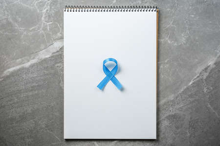 blue prostate ribbon on open notebook isolated on marble background, prostate cancer and symbol of helping HIV patients