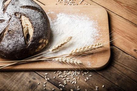 Brot auf dem Tisch, hausgemachtes Brot mit Mehl und Getreide auf Holzuntergrund Standard-Bild