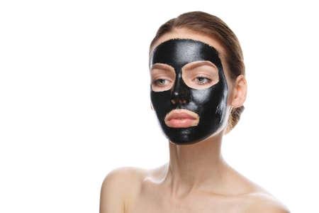 Mädchen mit schwarzer kosmetischer Maske im Gesicht, Gesichtsreinigung zu Hause isoliert auf weißem Hintergrund