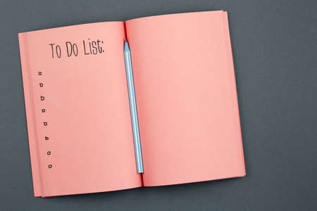 to do list Living Coral Notebook with pencil on gray background top view. blank notepad lies in the center of table, office concept flat lay. Stock Photo