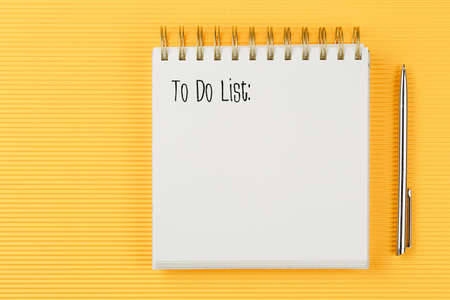 to do list notebook on corrugated yellow background with pen top view, spiral notepad with blank sheet, flat lay