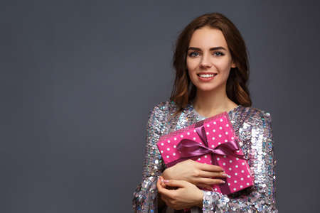 girl in a shiny New Years dress with a gift box with a heart. Birthday photo concept.