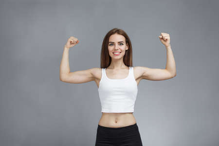 Portrait of pretty feminist woman shows her muscular arms proud from girl power and ready to face any challenges. strong lady fight with confident. Shows strength with raised hand, gray background