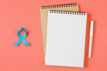 blue prostate ribbon on open notebook isolated on Living Coral background, prostate cancer and symbol of helping HIV patients