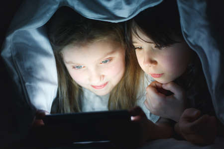 two girlfriends play on the phone under the covers, two little girls watch cartoons on the smartphone, sisters chat in chat Reklamní fotografie