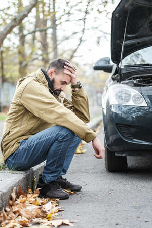 Bearded guy is repairing a car on the road, a car broke down on a trip