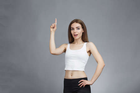 Beautiful girl shows finger pointed upwards at copy space and standing on gray background. lot of free space.