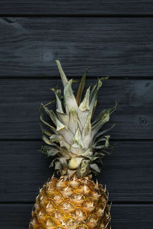 Ripe half pineapple with leaves on black wooden background. Close up image. Vertical photo. 版權商用圖片