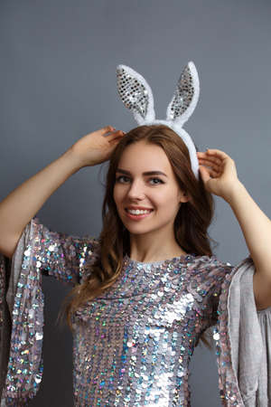 beautiful girl in a shiny dress with ears in her hair on a gray background. easter concept Zdjęcie Seryjne