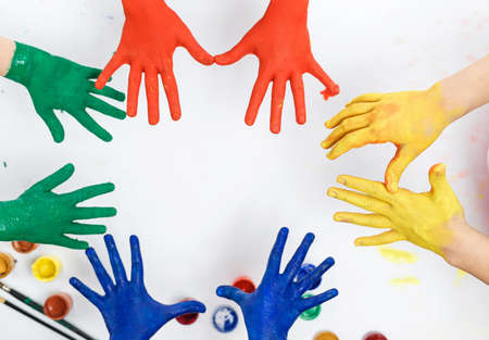 hands in paints on the background of a light table painted in different colors, childrens hands soiled in gouache paint top view