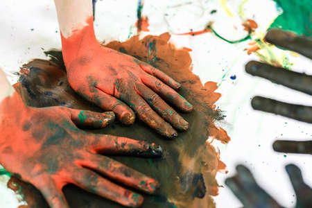 red hands in paints on the background of a light table painted in different colors, childrens hands soiled in gouache paint