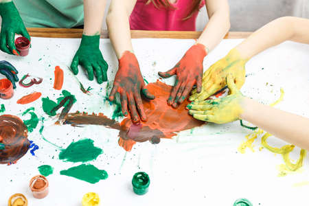 hands in paints on the background of a light table painted in different colors, childrens hands soiled in gouache paint