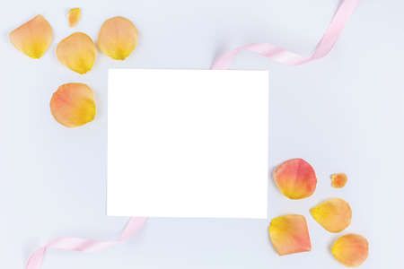 Sheet of white paper with Rose petals and pink ribbon. On blue isolated background. Love note. Romantic letter. concept Valentines Day
