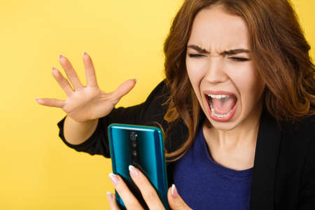 Angry woman shouting on smartphone, isolated on yellow background