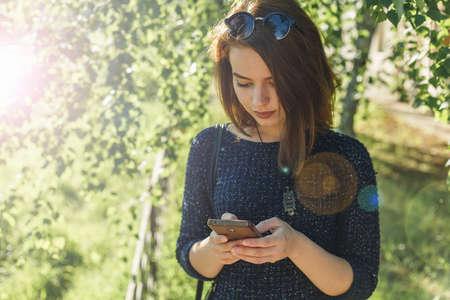 Beautiful happy girl correspond in social networks in a park on beautiful sun glare 版權商用圖片