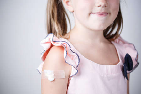 little girl with plaster on the shoulder from the injection, vaccinated in the shoulder, child vaccination, treatment of children patch