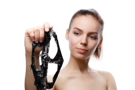 girl is holding a removed black cosmetic mask in her hands in front of her, isolated on a white background