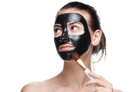 girl with black cosmetic mask on face, face cleaning at home isolated on white background 스톡 콘텐츠