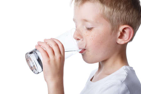 little boy drinks clean water from glass, adherence to balance of fluidity in body, photo isolated on white background