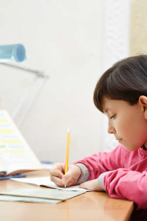 Little Asian schoolgirl doing homework while sitting at the desk at home. The girl writes with a pencil in a notebook. In the evening. Vertical photo.