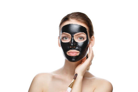 girl with a black cosmetic mask on her face holding a brush. mask made at home isolated on a white background 스톡 콘텐츠