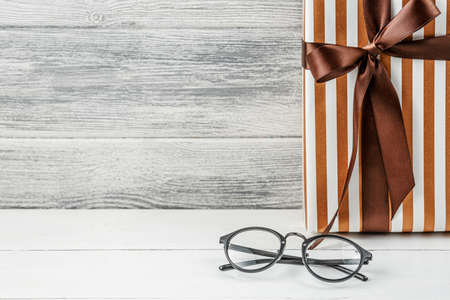gift and glasses on a wooden background. Concept of holiday.