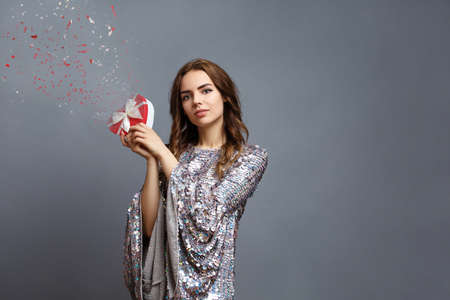 girl in a shiny New Years dress with a gift box with a heart. Valentines day concept. Birthday photo with the effect of broken glass. particle decomposition