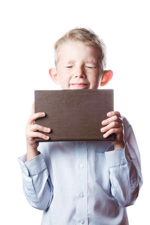 small boy screwed up his eyes and holds book in hands, portrait on isolated white background, schoolboy with book in hands