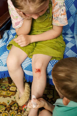 A little girl hurt her knee, a boy heals her wound. a scratched knee. brave girl Фото со стока - 140193420