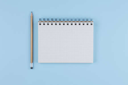 school notebook with a pencil on a blue table top view, office desktop, office supplies on a light blue background