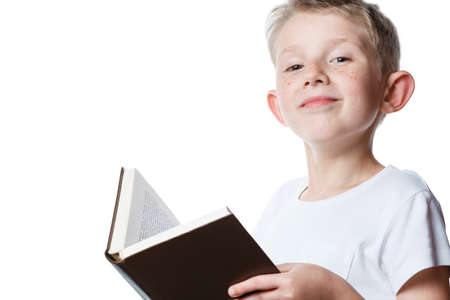 little boy reading book, portrait on isolated white background, schoolboy with book in hands