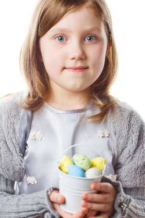 Girl with easter eggs in hands isolated on white background looking at camera and smiling. Concept of Easter