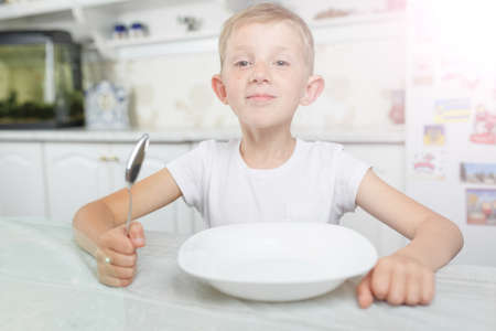 little boy in the kitchen eats, the child has breakfast at the table, a lot of light in the frame