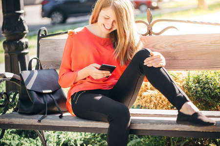 beautiful teenage girl with a backpack correspond with friends in social networks through a smartphone, a girl travels through Europe on a sunny day 版權商用圖片