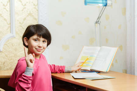 Smiling Asian schoolgirl doing homework while sitting at the desk at home. Studying at home according to the textbook. In the evening. She raise her index finger up. In the light of a desk lamp.