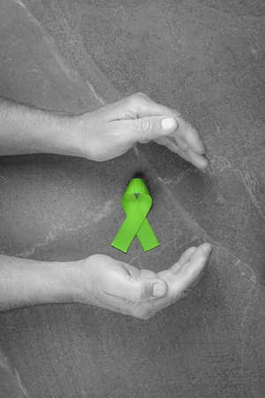 hands holding green ribbon, Lymphoma Cancer and mental health awareness, Gallbladder and Bile Duct Cancer. on dark gray background