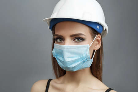 Young woman in medical mask and white construction helmet on a gray background.